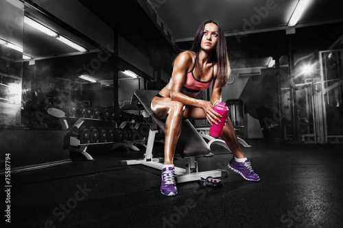 fitness girl with shaker posing on bench in the gym - 75587794