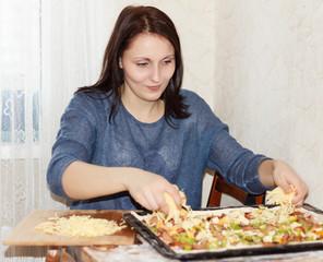 Brunette girl preparing a pizza
