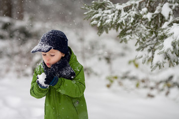 Adorable little boy, blowing snowflakes outside in a snowy day