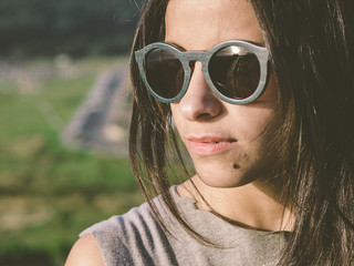 Brunette woman with sunglasses in a close up portrait