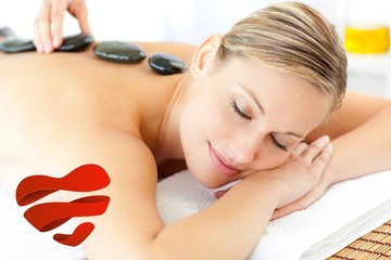 Composite image of relaxed woman having a massage
