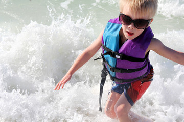 Young Child Playing in Ocean Waves in Life Jacket