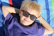 Happy Young Child Relaxing On Beach Towel with Sunglasses