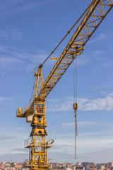 Yellow construction crane over city