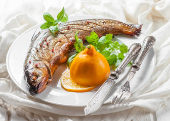 smoked whitefish with lemon and basil on a white plate