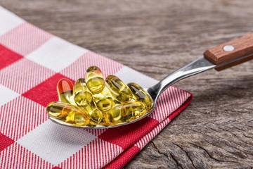 Tablespoon with dietary vitamin E pills. In napkin.