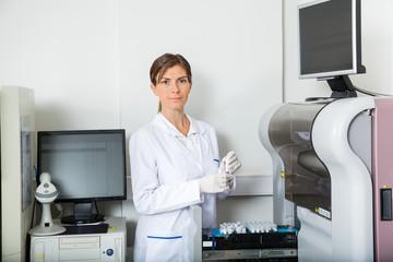 Scientist Loading Coagulation Analyzer With Samples