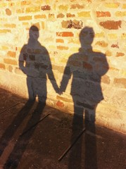Old wall with shadow of a couple holding their hands