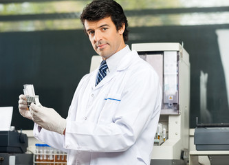 Confident Scientist Analyzing Urine Samples In Lab