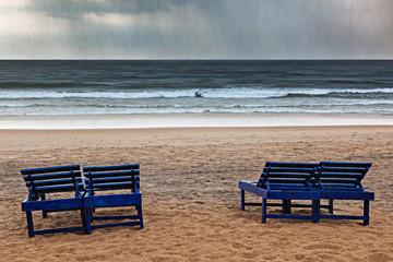 Beach chairs under rain