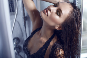 sexy woman with dark hair taking shower in lace lingerie
