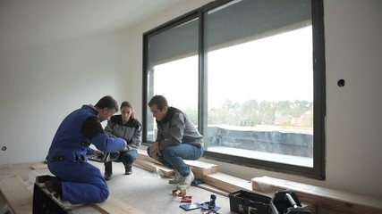 Carpenter with trainees installing wooden floor