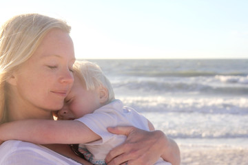 Young Child Protect Safely in Mother's Loving Embrace on Beach