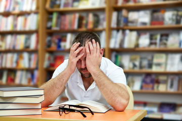 Tired man sleeping in the library
