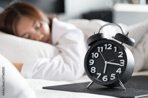 Leinwanddruck Bild Asian woman sleeping on bed and wake up with alarm clock