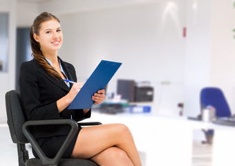 Businesswoman sitting on a chair and writing some documents