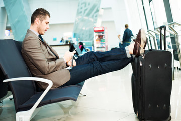 Businessman at airport with smartphone and suitcase