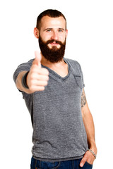 Happy Tattooed bearded man with thumbs up gesture, isolated on w