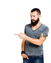 Happy Tattooed bearded man presenting and showing with copy spac