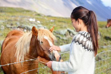 Icelandic horses - woman petting horse on Iceland