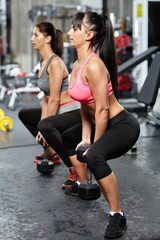 Girls doing dumbbell squats in a gym