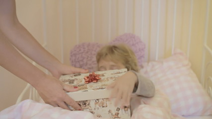 Little girl sick in bed gets gift close up