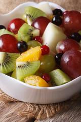 salad of oranges, kiwi, grapes and berries macro. vertical