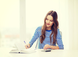 student girl with book, calculator and notebook