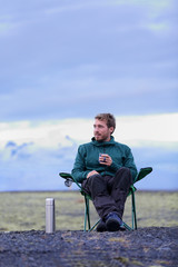 Camping man sitting in drinking coffee in nature