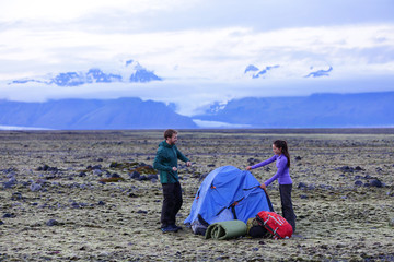 Camping couple pitching tent after hiking