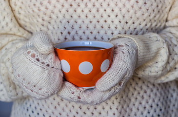 Hands in knitted mittens holding a cup of coffe