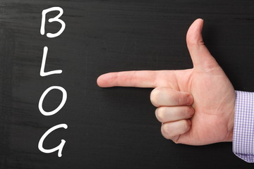 Hand pointing at the word BLOG on a blackboard