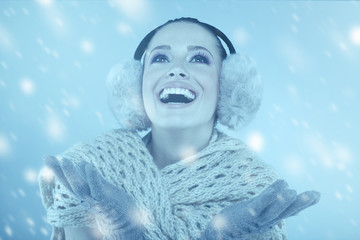 Woman in winter clothes catching snowflakes