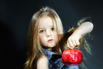 Cute little girl posing with red pomegranate