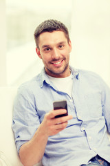 smiling man with smartphone at home