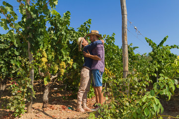 Young couple, vine growers, in the vineyard.