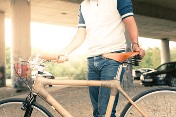 Man holding a bicycle in a sunny urban scene