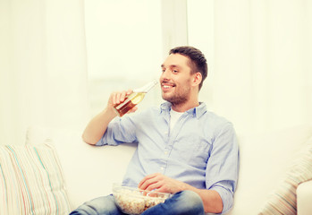 smiling man with beer and popcorn at home