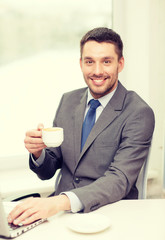 smiling businessman with laptop and coffee