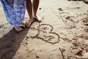 Young beautiful couple on the beach making heart