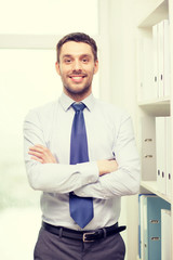 handsome businessman with crossed arms at office