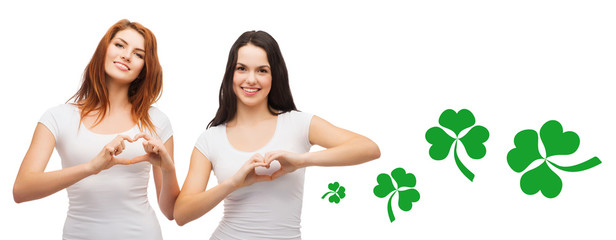 smiling girls showing heart gesture with shamrock