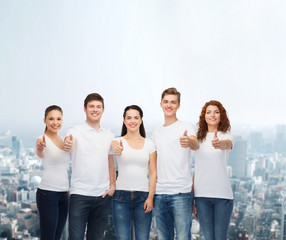 smiling teenagers in t-shirts showing thumbs up