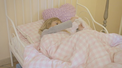 Little girl sick in bed plays with napkin