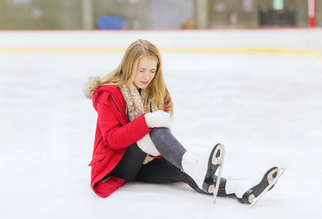 young woman fell down on skating rink
