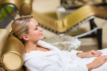 beautiful young woman sitting in bath robe at spa
