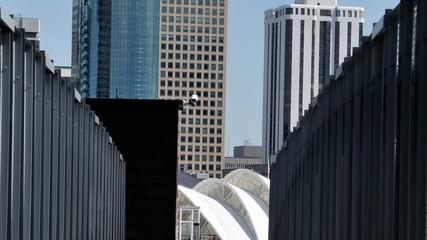 Tilt shot from pedestrian bridge to tall skyscrapers