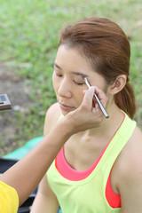 Closeup portrait of a woman having applied makeup by makeup arti