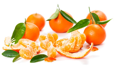 Fresh tangerine fruits with green leaves and slices.