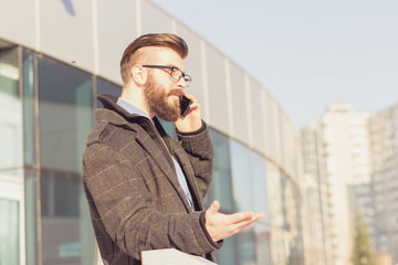 Frustrated young man with a beard talking by phone